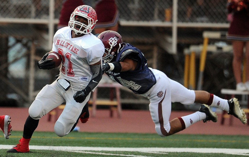 . Eest\'s Aaron Vaughns (21) (Charter Oak) runs for a 54 years touchdown past West\'s Christopher Mendoza (Bell Gardens) in the first half of the annual East vs. West San Gabriel Valley Hall of Fame all-star football game at West Covina High School on Friday, May 17, 2013 in West Covina, Calif. 