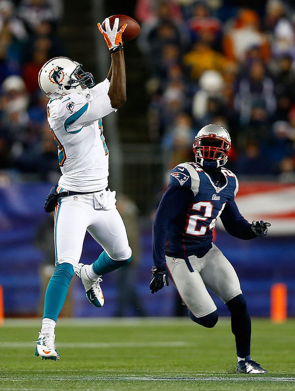 . Armon Binns #19 of the Miami Dolphins catches a pass in front of Kyle Arrington #24 of the New England Patriots in the second half during the game at Gillette Stadium on December 30, 2012 in Foxboro, Massachusetts. (Photo by Jared Wickerham/Getty Images)