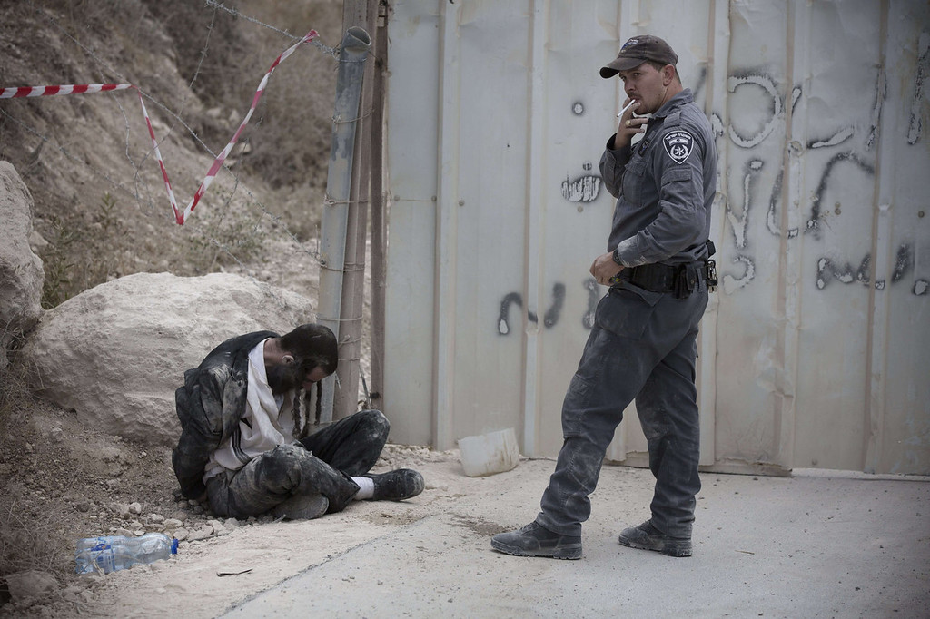 . An Ultra-Orthodox Jewish man is arrested by Israeli policemen in Ramat Beit Shemesh West of Jerusalem on August 12, 2013, after dozens of Haredim protest against desecration of ancient graves were discovered at a new housing construction site. Some 14 Ultra-orthodox Jews were arrested.  MENAHEM KAHANA/AFP/Getty Images