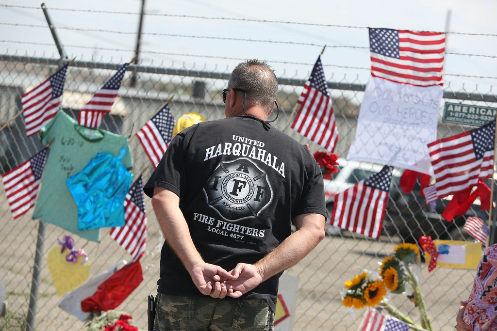 . Phoenix firefighter Mike Holliday pays his respects to the 19 Granite Mountain Hotshot firefighters in Prescott, Arizona July 2, 2013.  Reinforcements poured in Monday to battle a runaway wildfire which quadrupled in size overnight after killing 19 firefighters in one of the worst such incidents in US history. AFP PHOTO / KRISTA  Kennell/AFP/Getty Images