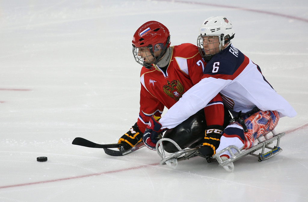 . Declan Farmer (R) of the USA fights for the puck with Nikolay Terentyev (L) of Russia during the Ice Sledge Hockey final  match at Sochi 2014 Paralympic Games, Russia, 15 March 2014.  EPA/SERGEI CHIRIKOV