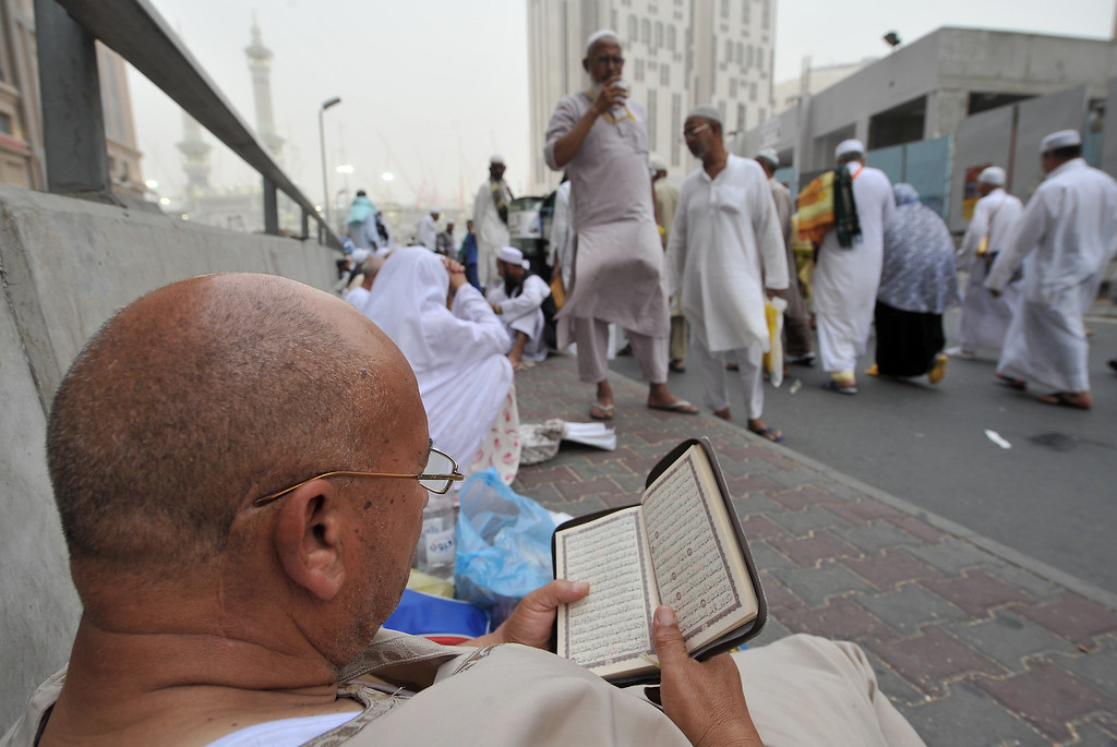 . A Muslim pilgrim reads a copy of the Koran as he waits to perform evening prayers in Mecca\'s Grand Mosque on October 8, 2013, as more than two million Muslims have arrived in the holy city for the annual hajj pilgrimage. The hajj, which is one of the world\'s largest human assembly, begins on October 13 amid concerns over the deadly MERS coronavirus. (FAYEZ NURELDINE/AFP/Getty Images)