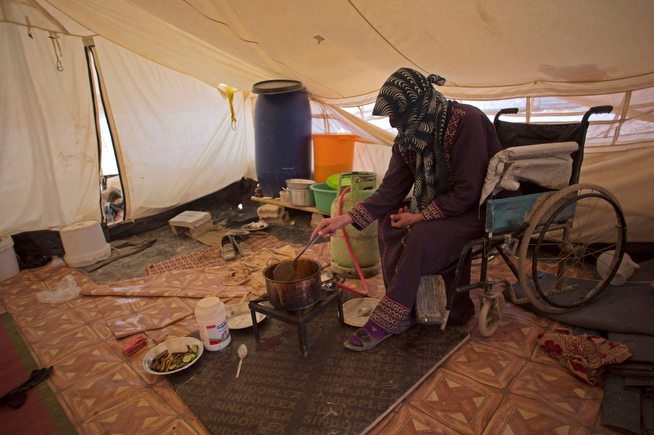. In this Thursday April 17, 2014 photo, Ghasibeh Kasabneh, 46, prepares food for the family, inside her tent at Zaatari Syrian refugee camp, near the Syrian border in Jordan. Zaatari is the region\'s largest camp for Syrian refugees. (AP Photo/Khalil Hamra)