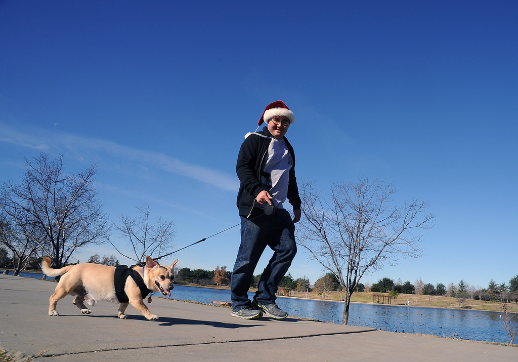 . Jeff Kan, North Hills, walks his dog Butter around Lake Balboa  at Anthony C. Beilenson Park in Van Nuys Christmas day. (Photo by Hans Gutknecht/Los Angeles Daily News)