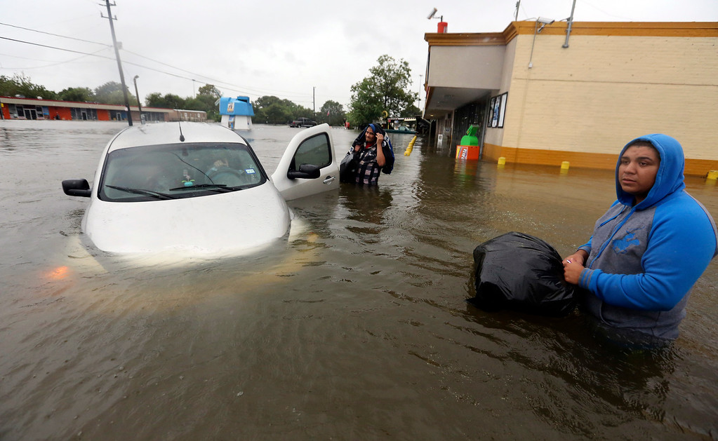 . Conception Casa, center, and his friend Jose Martinez, right, check on Rhonda Worthington after her car became stuck in rising floodwaters from Tropical Storm Harvey in Houston, Texas, Monday, Aug. 28, 2017. The two men were evacuating their home that had become flooded when they encountered Worthington\'s car floating off the road. (AP Photo/LM Otero)
