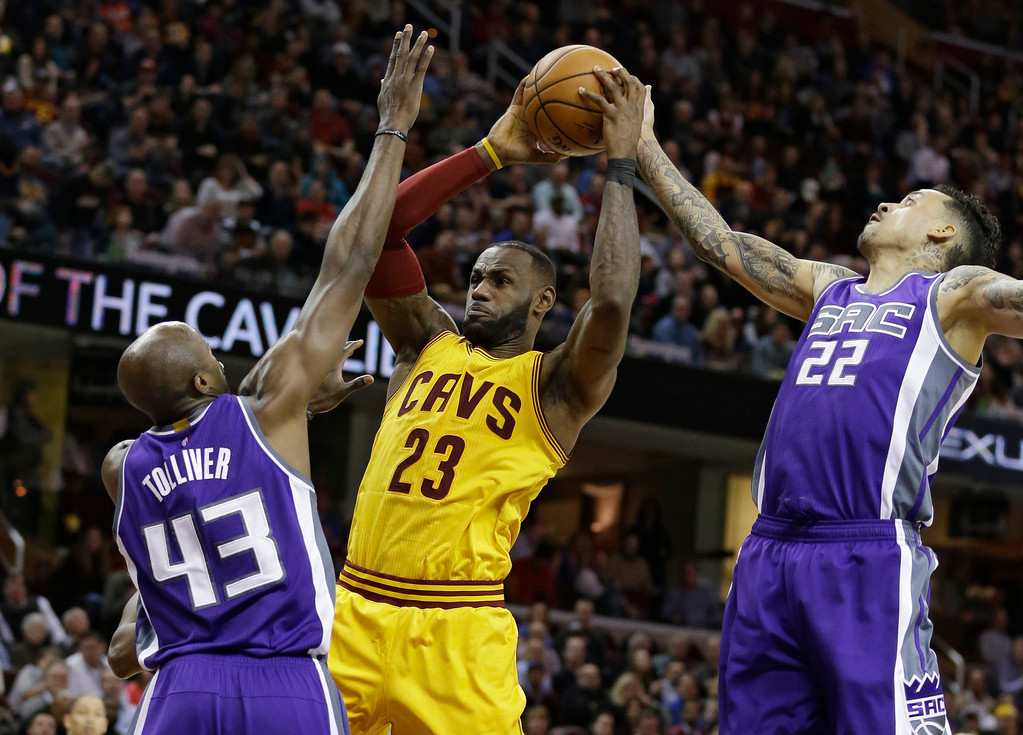 . Sacramento Kings\' Anthony Tolliver (43) and Matt Barnes (22) defend Cleveland Cavaliers\' LeBron James (23) during the second half of an NBA basketball game, Wednesday, Jan. 25, 2017, in Cleveland. The Kings won 116-112. (AP Photo/Tony Dejak)