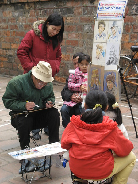 A couple girls get their picture drawn.