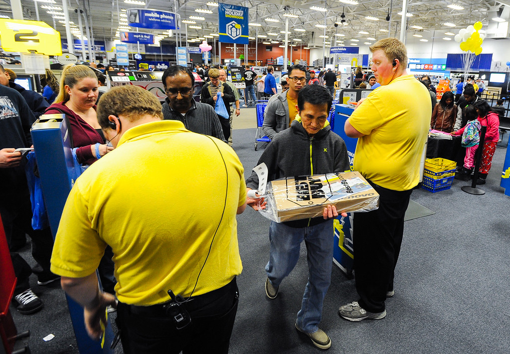 . Shoppers leave Best Buy with early Black Friday deals after the store opened its doors at 6 p.m. for early sales on Thanksgiving in San Bernardino on Thursday, Nov. 28, 2013. Many retail stores pushed the boundary the Black Friday tradition this year with offering Black Friday deals on Thanksgiving day. (Photo by Rachel Luna / San Bernardino Sun)