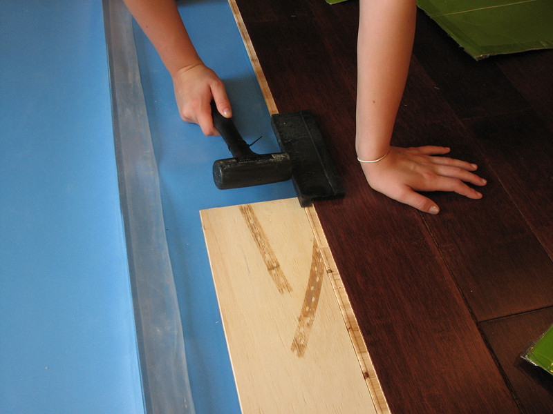 Alli demostrating the technique. One hand provides pressure at the crack. The board provides the angle (saving your fingers) and makes it easier for one person to do most of a row.