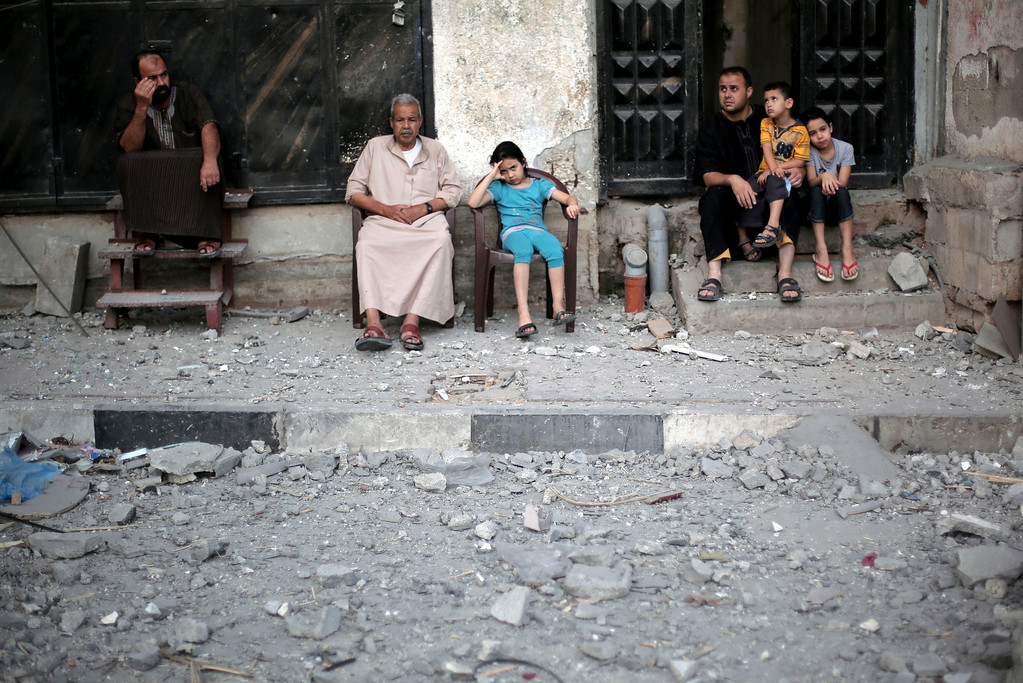 . Neighbors of Palestinian Hamas leader, Mahmoud Zahar, sit outside their homes following an early morning Israeli missile strike that destroyed Zahar\'s house in Gaza City, Wednesday, July 16, 2014. Israel on Wednesday intensified air attacks on Hamas targets in the Gaza Strip following a failed Egyptian cease-fire effort, targeting the homes of four senior leaders of the Islamic militant movement and ordering tens of thousands of residents to evacuate border areas. (AP Photo/Khalil Hamra)