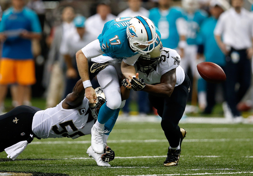 . Quarterback Ryan Tannehill #17 of the Miami Dolphins fumbles the ball as he is hit by middle linebacker Curtis Lofton #50 and the Saints recover in the second quarter at the Mercedes-Benz Superdome on September 30, 2013 in New Orleans, Louisiana.  (Photo by Chris Graythen/Getty Images)