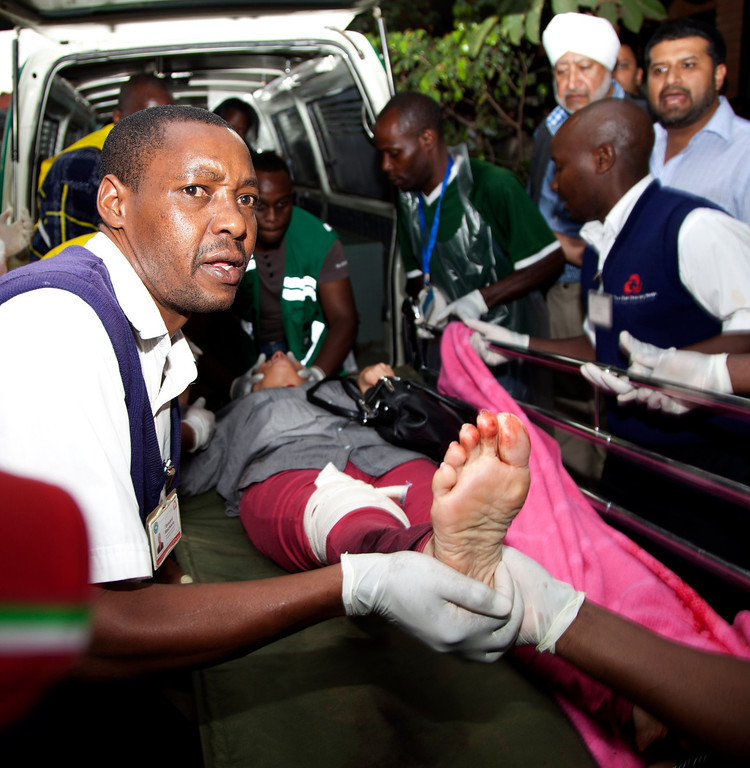 . An injured person is helped on his arrival at the Aga Khan Hospital in Nairobi after an attack at the Westgate Mall, an upscale shopping mall in Nairobi, Kenya Saturday Sept. 21, 2013, where shooting erupted when armed men staged an attack. (AP Photo/Jason Straziuso)