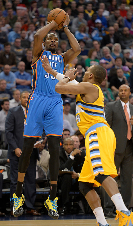 . Oklahoma City Thunder small forward Kevin Durant (35) goes up for two of his game high 30 as he takes a shot over Denver Nuggets shooting guard Randy Foye (4) December 17, 2013 at Pepsi Center. (Photo by John Leyba/The Denver Post)