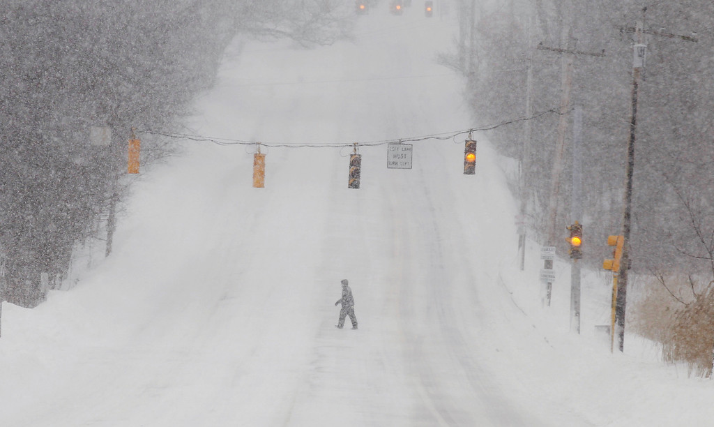 . A pedestrian crosses a deserted street in North Andover, Mass. Saturday, Feb. 9, 2013 after a snowstorm came through dumping more than 2 feet of snow on New England. (AP Photo/Winslow Townson)