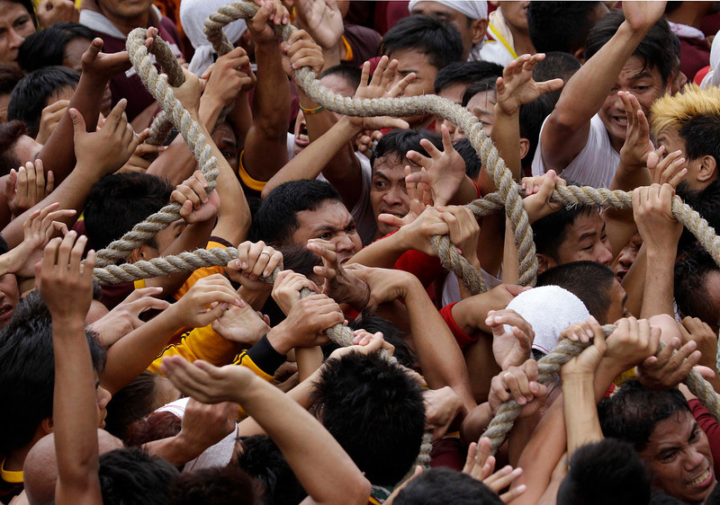 . Devotees scramble to grab the rope that pulls the cart of the centuries-old image of the Black Nazarene during a raucous procession Wednesday, Jan. 9, 2013, in Manila, Philippines. Hundreds of thousands of mostly barefoot Roman Catholic devotees joined the annual ritual to demonstrate faith and seek miracle cures for illnesses and a good life. (AP Photo/Aaron Favila)