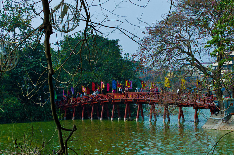 """The Huc Bridge, a very scenic red lacquered timber bridge, is situated at the north-eastern corner of Hoan Kiem Lake – a tranquil setting in the heart of Hanoi's Old Quarter. The """"Flood of Morning Sunlight"""" provides views towards Turtle Island and access to the Ngoc Son Temple.  http://www.virtualtourist.com/travel/Asia/Vietnam/Thu_Do_Ha_Noi/Hanoi-1481679/Things_To_Do-Hanoi-Hoan_Kiem_Lake-BR-1.html"""