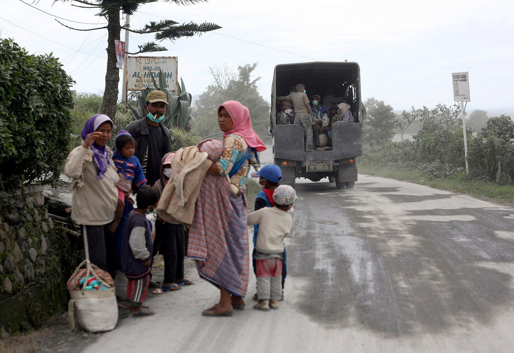 . Villagers wait for evacuation on a road covered by volcanic ash from an eruption of Mount Sinabung as they flee their homes in Karo, North Sumatra, Indonesia, Sunday, Sept. 15, 2013. Thousands of people fled their homes after the volcano erupted early Sunday.   (AP Photo/Binsar Bakkara)