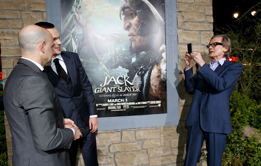 ". Cast member Bill Nighy takes a photo of co-stars Stanley Tucci (L) and Nicholas Hoult at the premiere of ""Jack the Giant Slayer\"" in Hollywood, California February 26, 2013. The movie opens in the U.S. on March 1.  REUTERS/Mario Anzuoni"
