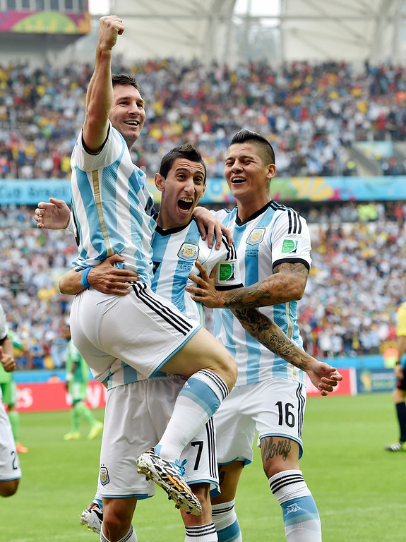 . Argentina\'s Lionel Messi, left, is carried by his teammates Argentina\'s Angel di Maria (7) and Marcos Rojo (16) after scoring his side\'s first goal during the group F World Cup soccer match against Nigeria at the Estadio Beira-Rio in Porto Alegre, Brazil, Wednesday, June 25, 2014. (AP Photo/Martin Meissner)