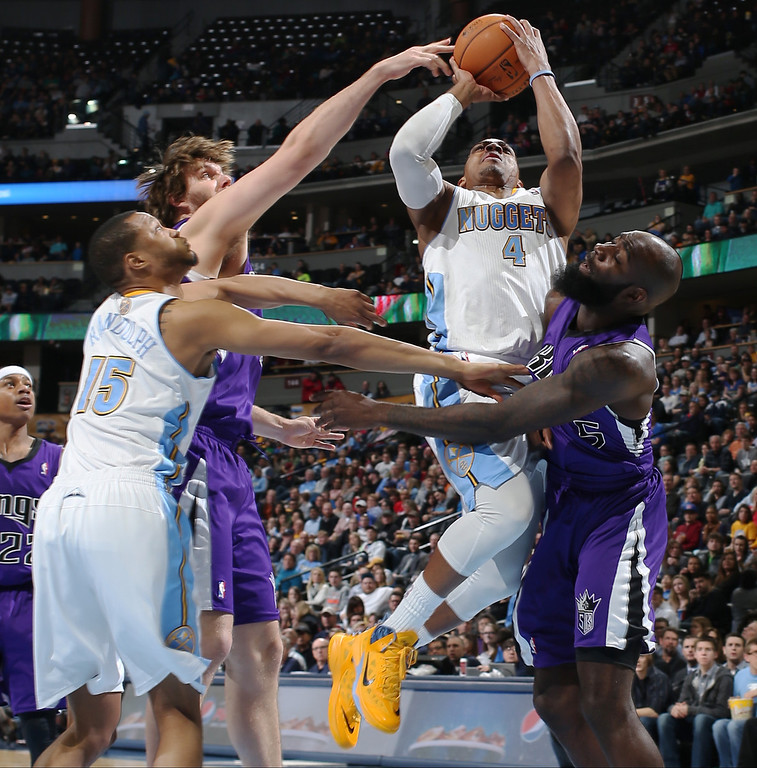 . Denver Nuggets guard Randy Foye, third from left, drives for a shot as Sacramento Kings center Aaron Gray, second from left, and forward Quincy Acy cover in the fourth quarter of an NBA basketball game in Denver, Sunday, Feb. 23, 2014. Nuggets forward Anthony Randolph, far left, looks on. The Kings won 109-95. (AP Photo/David Zalubowski)