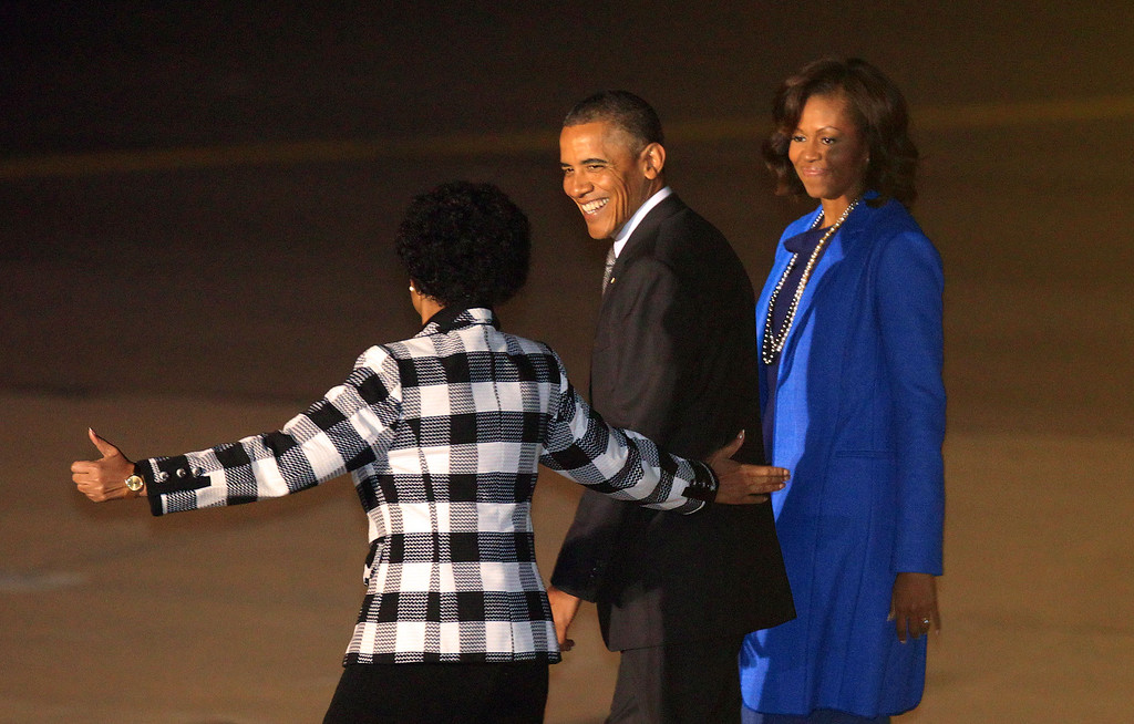 . U.S. President Barack Obama, middle, and first lady Michelle Obama, right, react as Maite Nkoana-Mashabane, Minister of International Relations and Cooperation, left, gestures during their arrival at Waterkloof Airbase in Pretoria, Friday, June 28, 2013. President Obama is receiving the embrace you might expect for a long-lost son on his return to his father\'s home continent, even as he has yet to leave a lasting policy legacy for Africa on the scale of his two predecessors. (AP Photo/Themba Hadebe)