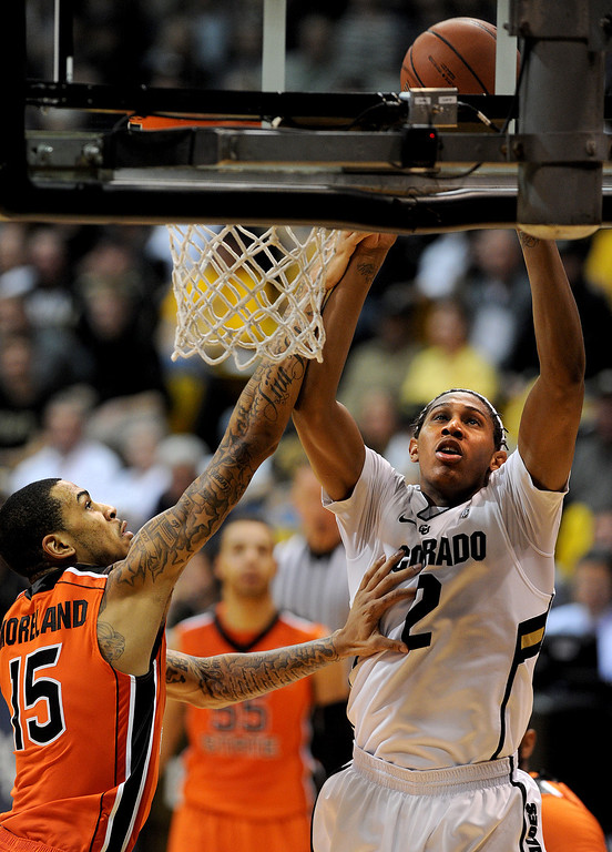 . Xavier Johnson of CU scores past Eric Moreland of OSU during the second half of the March 9, 2013 game in Boulder.    (Cliff Grassmick/Boulder Daily Camera)