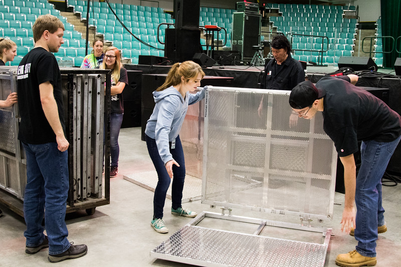CUB members setting up metal barricades to go in front of the stage.