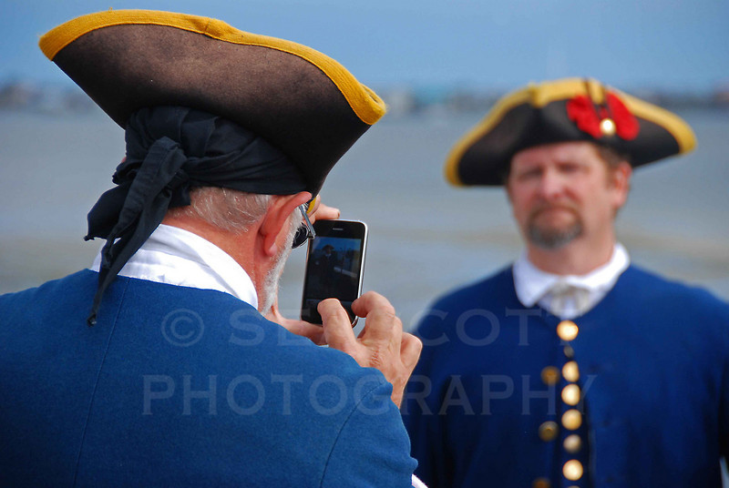 Guards In period dress at Castillo de San Marcos make use of modern technology.  St. Augustine, FL.