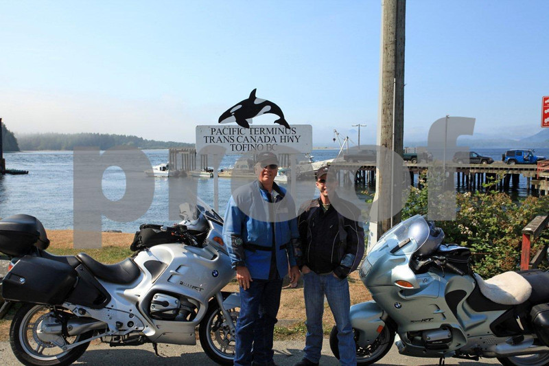 Two bikers pose at the Pacific Terminus of Trans Canada Highway inTofino on Vancouver Island in British Columbia.