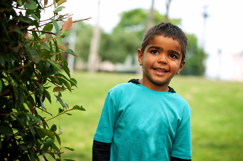Little Aboriginal Boy next to a Bush