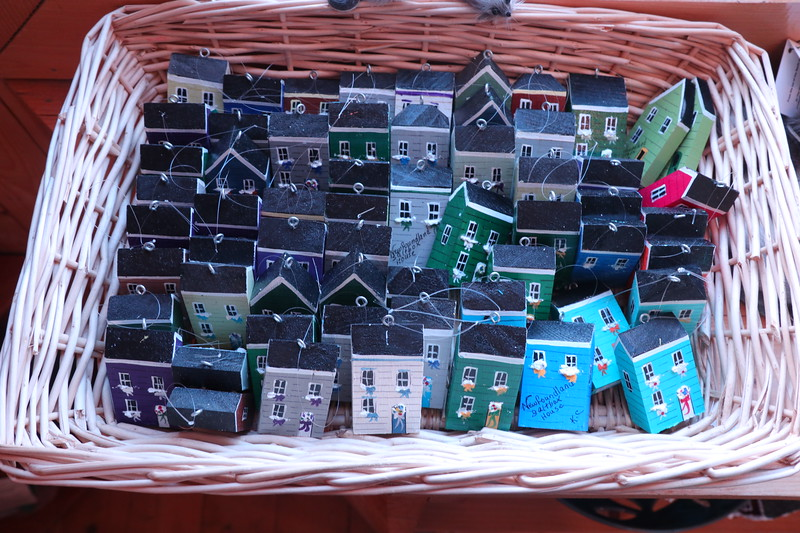 Colorful Newfoundland homes in a basket.  Practical door stops and paper weights