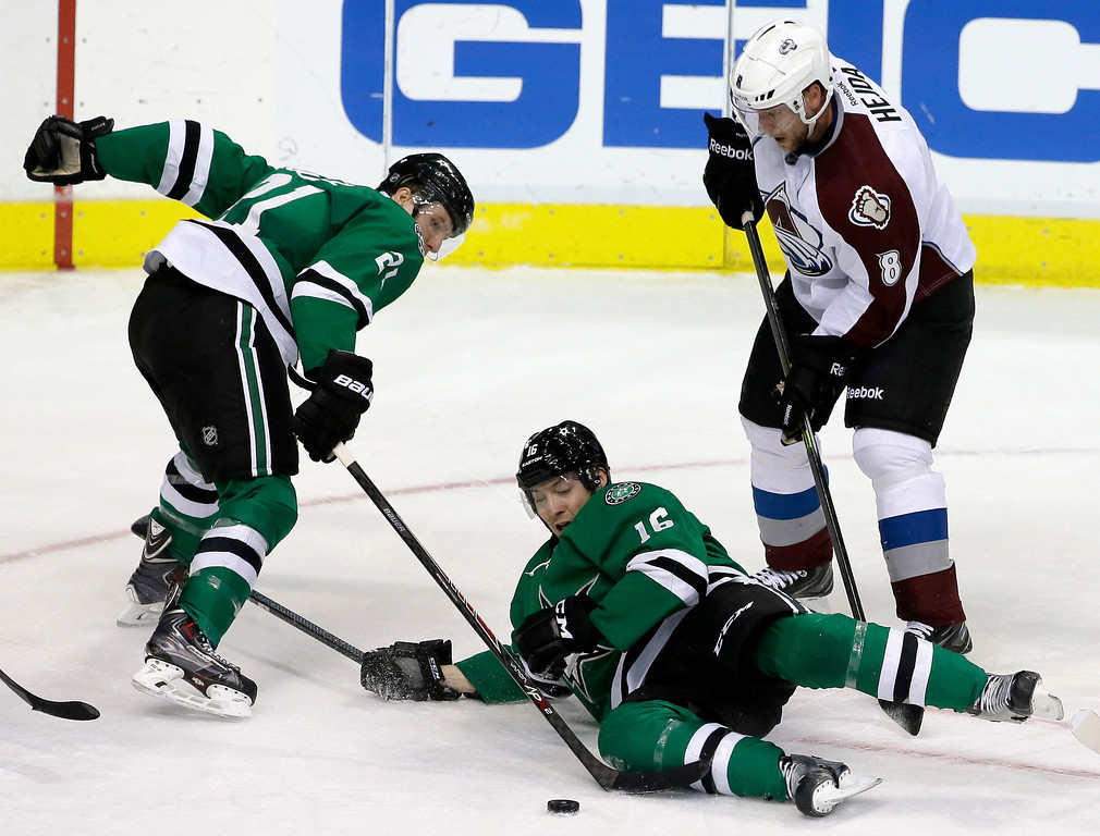 . Dallas Stars left wing Antoine Roussel (21), of France, and Ryan Garbutt (16) attempt to gain control of a loose puck in front of Colorado Avalanche\'s Jan Hejda (8), of Czech Republic, in the third period of an NHL hockey game, Monday, Jan. 27, 2014, in Dallas. The Avalanche won 4-3. (AP Photo/Tony Gutierrez)