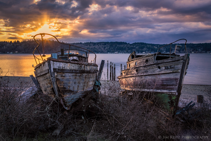 Weathered old boats on Bainbridge Island, as the sunset breaks thru the clouds.