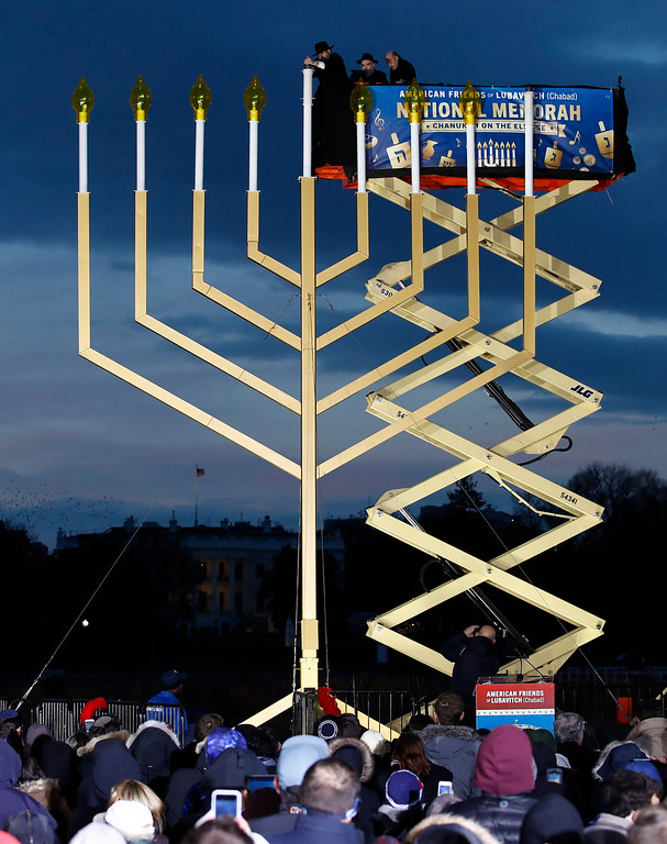 . From left, Rabbi Levi Shemtov, Rabbi Abraham Shemtov, and National Economic Director Gary Cohn, light the Menorah during the annual National Menorah Lighting, in celebration of Hanukkah, on the Ellipse near the White House in Washington, Tuesday, Dec. 12, 2017. (AP Photo/Carolyn Kaster)