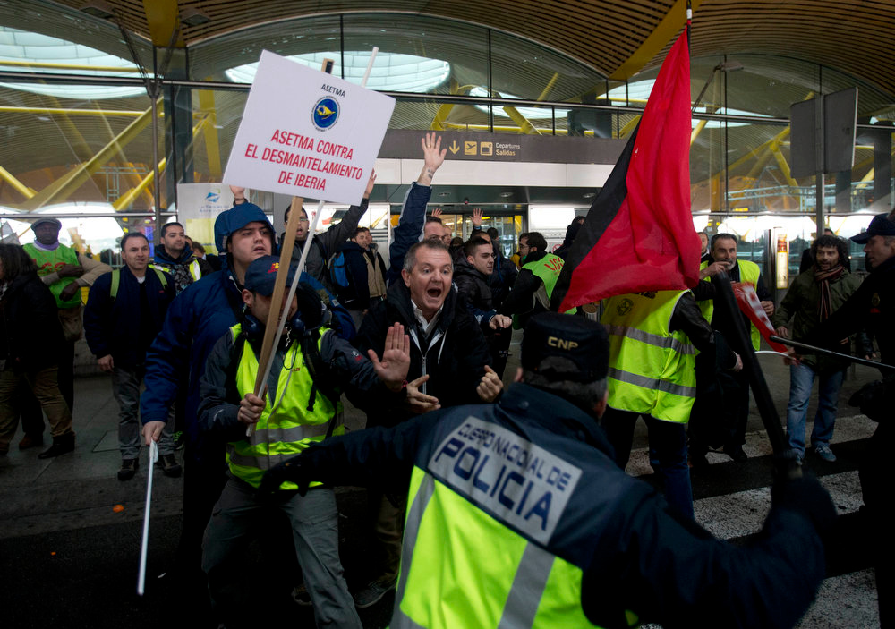 . Police baton charge Iberia workers outside  Barajas international airport in Madrid, Spain Monday Feb. 18, 2013, as ground staff and cabin crews for Spain\'s Iberia begin 15-days of strikes to protest plans to lay off 3,800 staff.  The company, which is looking to cut jobs after it reported substantial losses last year, says the stoppages will lead to more than 1,200 flight cancellations over the next three weeks. The government has called on the company and unions to reach an agreement and end the strike. Banner reads \' Asetma (a trade union) against the dismantling of Iberia\' (AP Photo/Paul White)