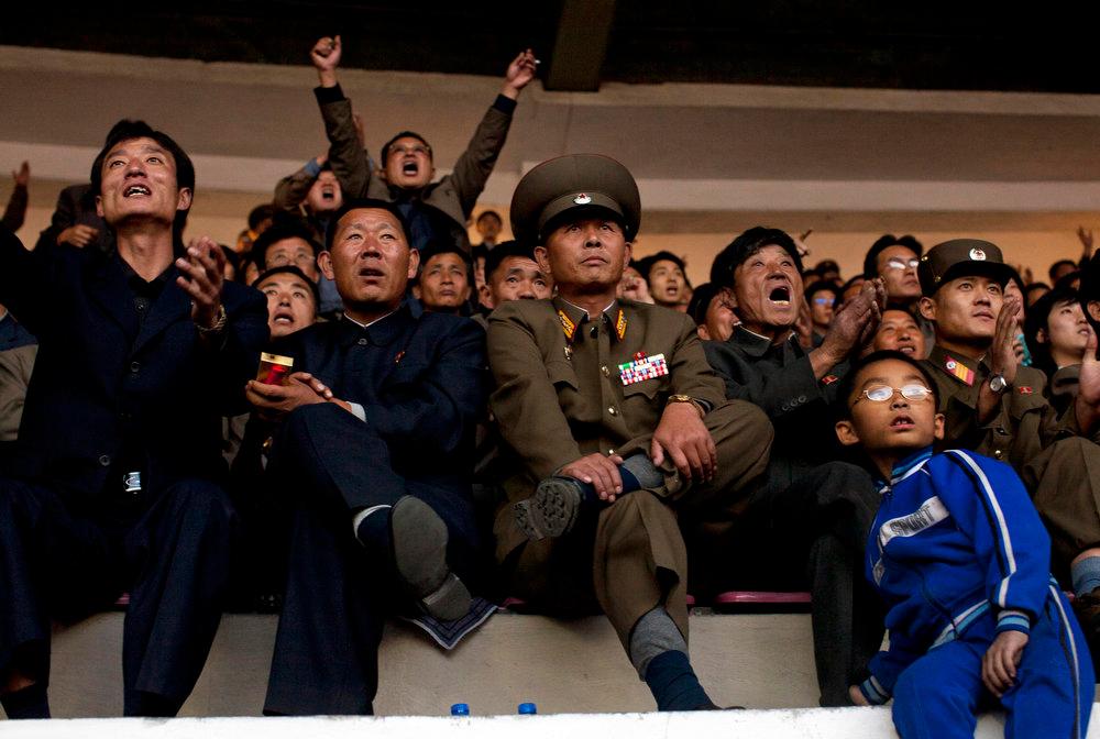 Description of . North Korean soccer fans cheer for their national team during a World Cup qualifying match between North Korea and Uzbekistan at Pyongyang's Yanggakdo Stadium, North Korea on Tuesday Oct. 11, 2011.  (AP Photo/David Guttenfelder)