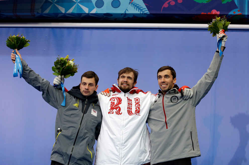 . From left to right silver medalist Martins Dukurs of Latvia, gold medalist Alexander Tretiakov of Russia and bronze medalist Matthew Antoine of the United States pose during the flower ceremony after the men\'s skeleton competition at the 2014 Winter Olympics, Saturday, Feb. 15, 2014, in Krasnaya Polyana, Russia. (AP Photo/Natacha Pisarenko)