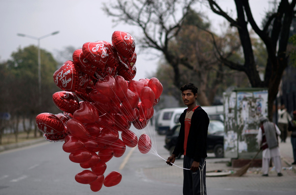 . A Pakistani man stands on a roadside waiting for customers to sell heart-shaped balloons on Valentine\'s Day, in Islamabad, Pakistan, Thursday, Feb. 14, 2013. Romance may not be dead in Pakistan but it is under attack. Conservatives in Pakistan are attacking the romantic holiday as a western-inspired event helping to spread vulgarity in their country and putting up posters calling on people to boycott the holiday. But romantics are fighting back with an arsenal of flowers, pink teddy bears and heart-shaped balloons. (AP Photo/Muhammed Muheisen)