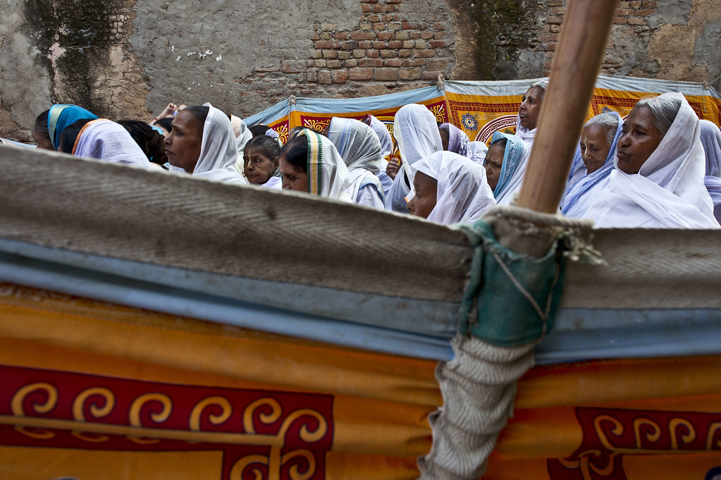 . Indian residents living in the Mahila ashram, a home for widows, walk along a cloth-lined street outside the ashram as they head to the waters of a Yamuna river to participate in a celebration for the Hindu festival Diwali in the northern city of Vrindavan on October 21, 2014. ROBERTO SCHMIDT/AFP/Getty Images