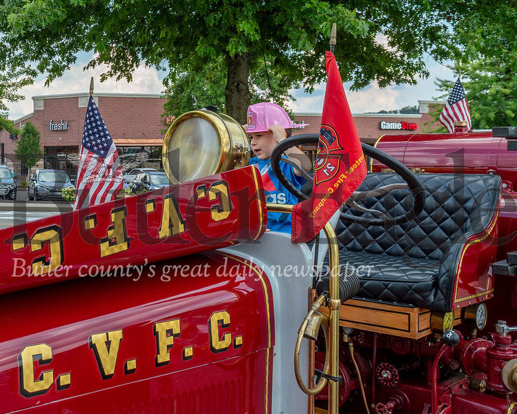 Luca Dowd holds onto his hat climbing in an old Cranberry Fire Department wagon at the township's National Night Out festivities Tuesday night, Aug. 6. Photo by Alex Weidenhof.