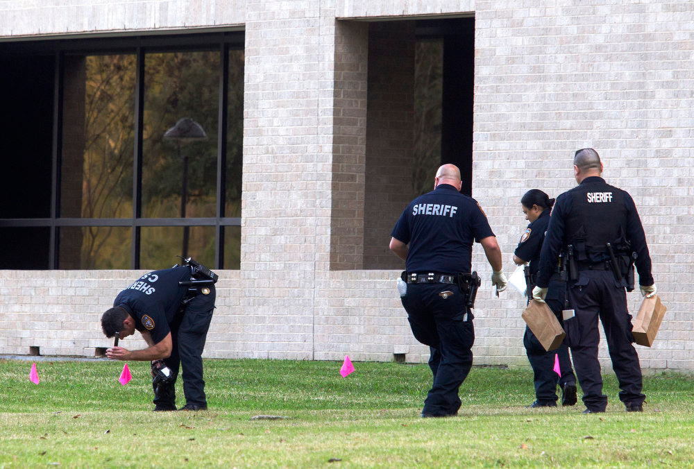 Description of . Police collect evidence after a shooting happened on Lone Star College North Harris campus on Tuesday January 22, in Houston. The shooting at a community college wounded three people Tuesday and sent some students fleeing for safety while others with medical training helped tend the wounded.   (AP Photo/ Patric Schneider)