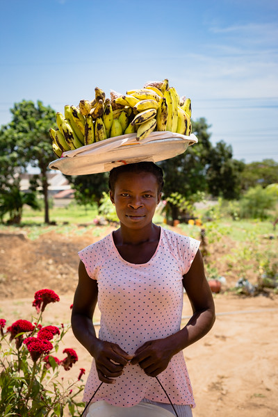 A produce seller at a roadside flower shop carries plantains. Sellers carry heavier loads with the assistance of baskets on top of their heads.