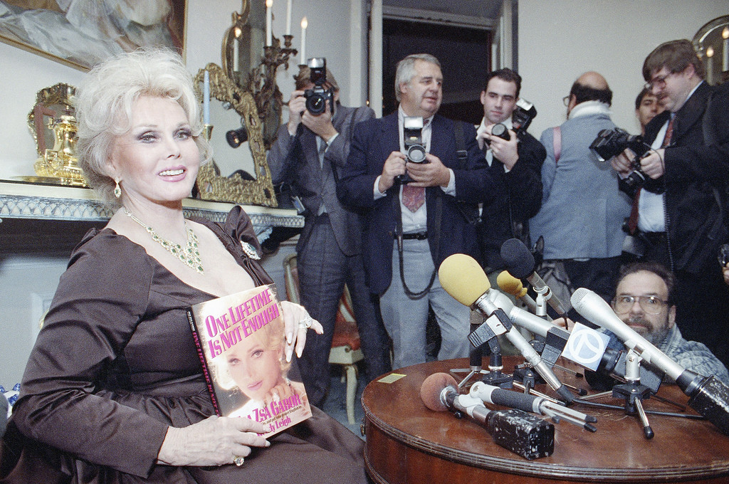 ". International film star Zsa Zsa Gabor, who gained notoriety by slapping a Beverly Hills police officer, announced on Nov. 19, 1991, Tuesday at her home in the Bel Air section of Los Angeles the publishing of her autobiography.    She holds her book,  ""One Lifetime is Not Enough,\"" in which she speaks out about her many marriages and lovers. (AP Photo/Chris Martinez)"