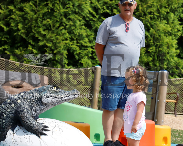 Jennie Langill, 2, of Cranberry strikes up a conversation with one of the crocodiles Crocodile Cove Playground in North Boundary Park in Cranberry, with her grandfather Denny Nollinger Wednesday. Seb Foltz/Butler Eagle 07/31/19