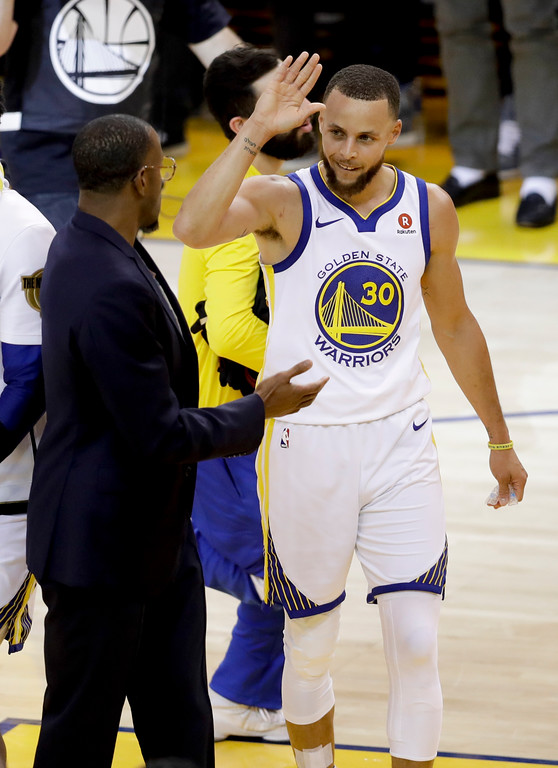 . Golden State Warriors guard Stephen Curry (30) is congratulated by injured forward Andre Iguodala, in suit, and teammates after scoring against the Cleveland Cavaliers during the first half of Game 1 of basketball\'s NBA Finals in Oakland, Calif., Thursday, May 31, 2018. (AP Photo/Marcio Jose Sanchez)