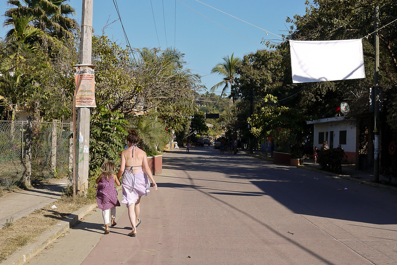 Victoria and her tiny friend skip down the streets in San Pancho, Mexico.