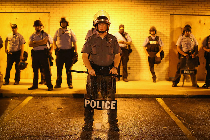 . Police stand guard before the mandatory midnight curfew on August 16, 2014 in Ferguson, Missouri. The curfew was imposed on Saturday in an attempt to reign in the violence that has erupted nearly every night in the suburban St. Louis town since the shooting death of teenager Michael Brown by a Ferguson police officer on August 9.  (Photo by Scott Olson/Getty Images)