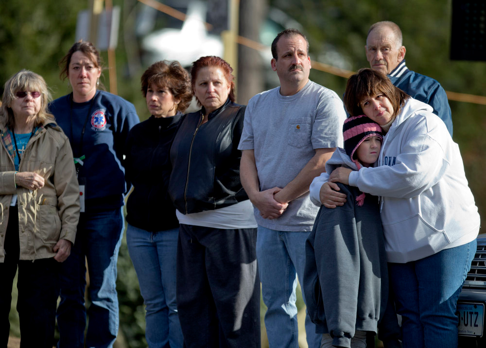 Description of . Mourners watch as the funeral procession of 7-year-old Sandy Hook Elementary School shooting victim Daniel Gerard Barden, passes the fire station outside the school's entrance, Wednesday, Dec. 19, 2012, in Newtown, Conn. (AP Photo/David Goldman)