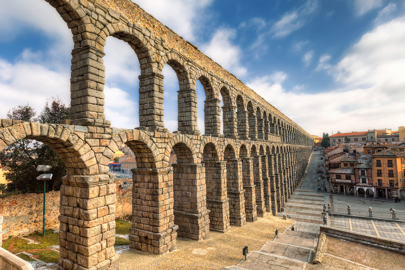 Aqueduct of Segovia  I had no luck for a nice light in Segovia. The day was quite cold and cloudy. Only later the sky cleared a little, but still, the light was horrible. But I tried my best. I actually edited this photo 2 times, as I was so dissatisfied with the first result, that I deleted it and started once more :)  Get more info about this photo on my blog http://blog.hdrshooter.net