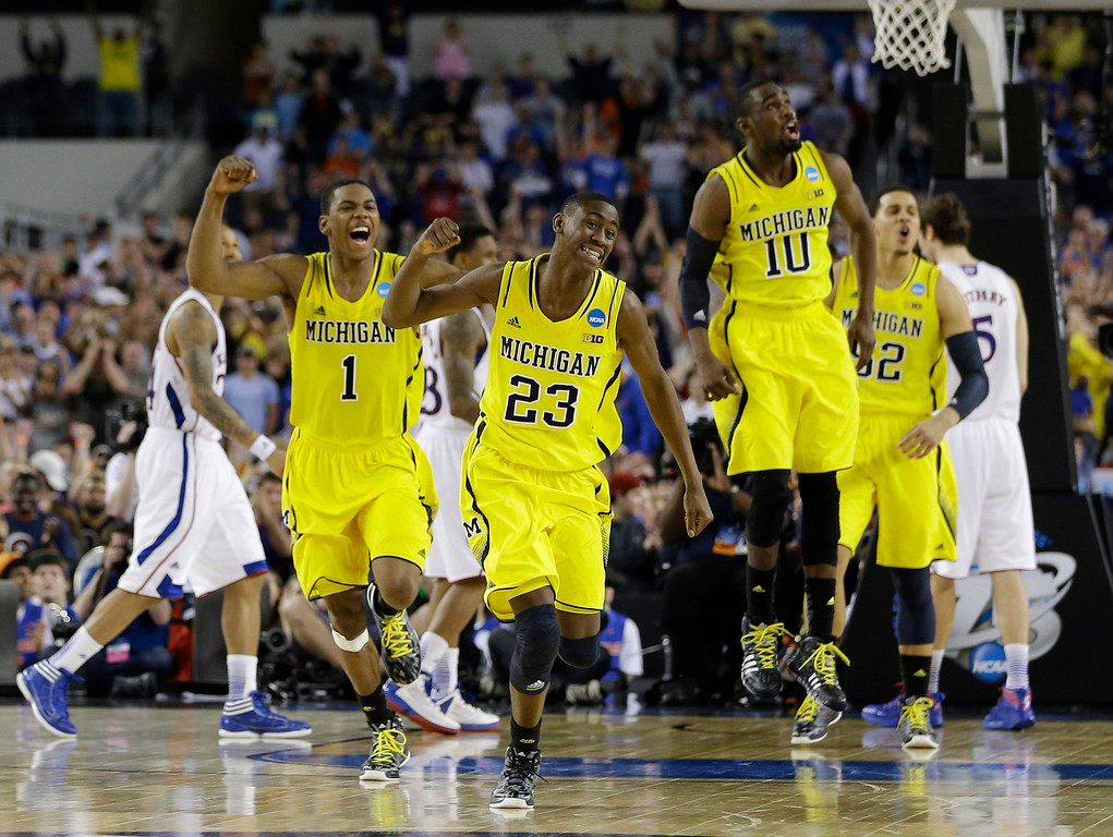 . Michigan celebrates after beating Kansas  87-85 in overtime of a regional semifinal game in the NCAA college basketball tournament, Friday, March 29, 2013, in Arlington, Texas. (AP Photo/David J. Phillip)